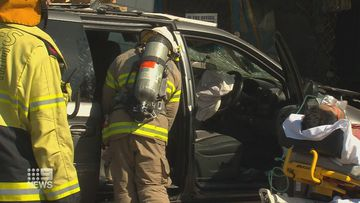 Emergency workers treat the driver at the scene of the crash in Adelaide.