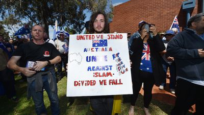 An anti-Islamic Reclaim Australia protester holding a placard at today's rally in Melton. (AAP)