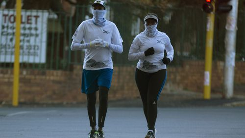 People jog wearing makeshift masks to protect against coronavirus, in Johannesburg, Friday, May 1, 2020.