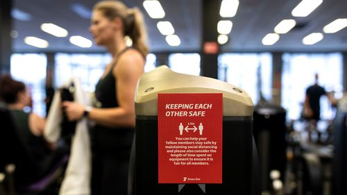 A sign warns gym-goers to social distance while working out