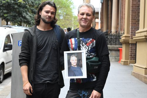 Daniel Sims (left) and Dustin Mileham hold a photo of their brother Donovan Mileham outside the Supreme Court in Sydney.
