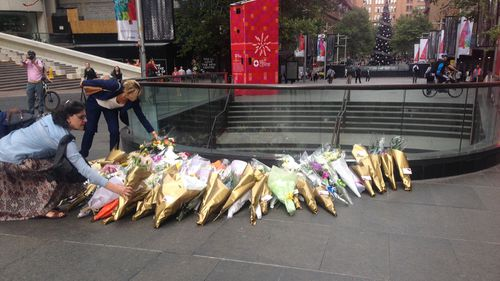 Every day a line would build down Martin Place. City workers, mothers with prams and toddlers, families, teenagers and grandparents all waiting patiently to place their flowers and their messages to the Johnson and Dawson families.
