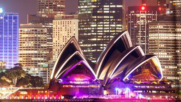 The Sydney Opera House and Sydney's skyline at night.