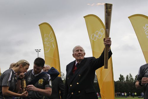Sir Roger Bannister holds the Olympic Flame on the running track at Iffley Road Stadium in Oxford, England. (AAP)