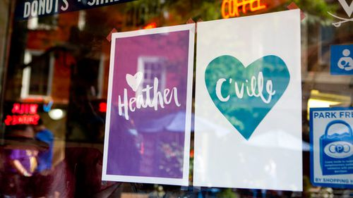 Signs hang in the window of a cafe in support of Heather Heyer at the Downtown Mall in Charlottesville. (AAP)