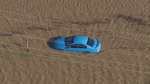 A car partially submerged in floodwaters at Jimboomba. (9NEWS)