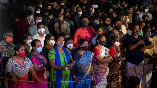 People wearing masks as a precaution against the coronavirus listen to a communist party rally in Kerala, India.