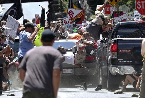 In this Aug. 12, 2017, file photo, people fly into the air as a vehicle is driven into a group of protesters demonstrating against a white nationalist rally in Charlottesville, Va. Federal hate crime charges have been filed against James Alex Fields Jr., accused of driving the car. (Ryan M. Kelly/The Daily Progress via AP, File)