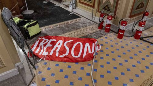 A banner reading 'Treason' is left on the floor of the US Capitol.