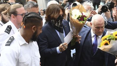 Actor Johnny Depp, centre, receives flowers as he arrives at the High Court for a hearing in his libel case, in London, Friday, July 24, 2020