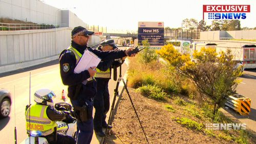 An officer with a digital stills camera using a high-powered zoom lens sets up where he can see city-bound peak hour traffic and photograph drivers doing the wrong thing.