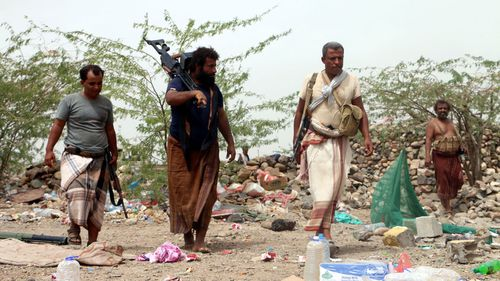 Members of Yemeni government forces take position during an offensive against Houthi positions on the outskirts of the western port city of Hodeidah.