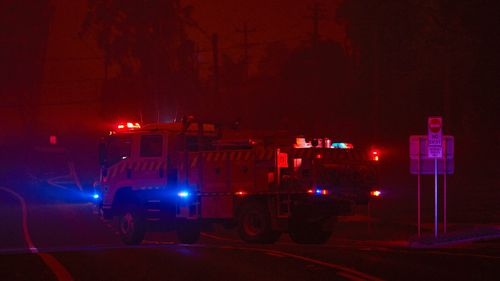 A fire truck leaves the local RFS station as thick smoke turns the town into darkness on January 04, 2020 in Bodalla, Australia.