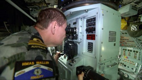 A crew member uses a periscope to scan for threats. (9NEWS)