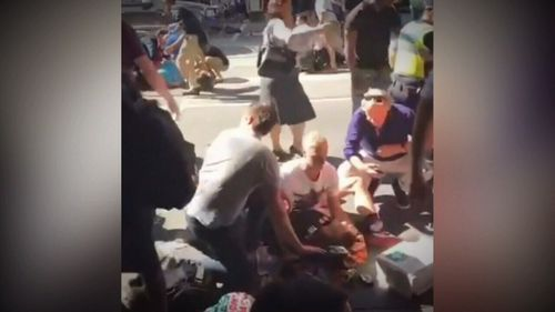 Bec is supported by bystanders in this image of the Flinders Street aftermath.