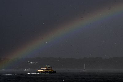 Brief sunshine in between storms brought out a rainbows above a Sydney ferry.