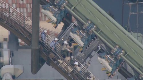 Sixty-four passengers were left hanging, about 30m from the ground. (NHK / AP)