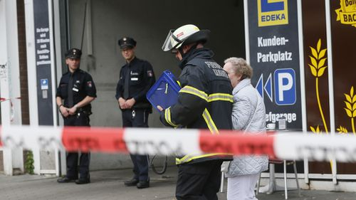 An elderly woman is accompanied by a firefighter after a knife attack at a supermarket in Hamburg, Germany, 28 July 2017. (AFP)