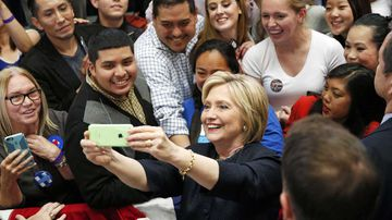Hillary Clinton takes a selfie with supporters. (AAP)