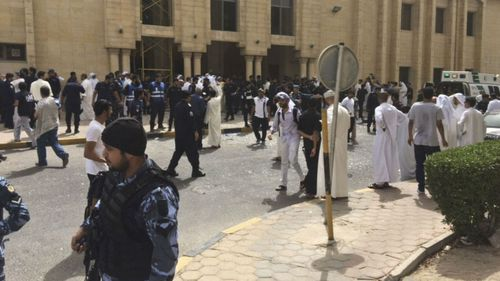 Security forces, officials and civilians gather outside of the Imam Sadiq Mosque in Kuwait City. (AAP)