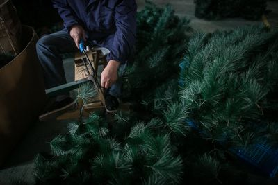 A Chinese worker cuts decorations for Christmas trees into pieces at a factory.
