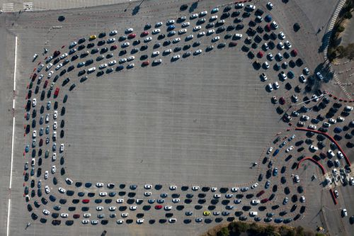 Motorists line up to take a coronavirus test in a parking lot at Dodger Stadium