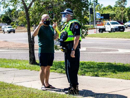 A man talks to a policeman outside a COVID-19 testing station at Marrara Sport Complex in Darwin.