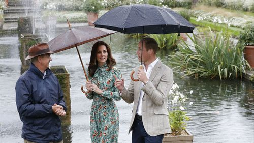 Prince William, right, and his wife Kate, Duchess of Cambridge are given a tour at the memorial garden in Kensington Palace. (AAP)
