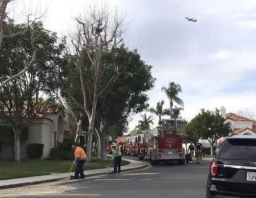 Crews clean up where a helicopter crashed into a house in Newport Beach yesterday. (AAP)