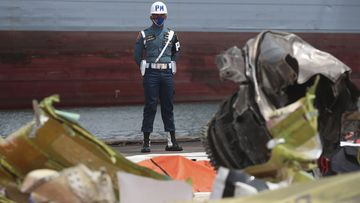 An Indonesian soldier stand guard near debris found in the waters around the location where a Sriwijaya Air passenger jet crashed at the search and rescue command centre at Tanjung Priok Port in Jakarta, Indonesia, Friday, Jan 15, 2021