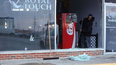 A man sweeps away glass and debris at his Ferguson hair dressing salon after rioters damaged the business. (AAP)