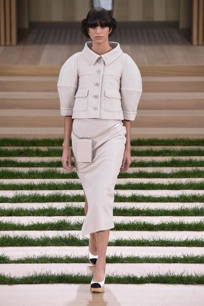 """<p>To showcase its haute couture collection, Chanel had models meander through an impeccably neat garden in chignons and two-tone platforms while wielding iPhone 6 cases that matched their outfit. </p><p>Sticking with a beige palette (""""Gabrielle Chanel was the Queen of beige,"""" said Karl Lagerfeld backstage), sleeveless evening dresses were accompanied by show-stealing rhinestone capes.</p><p>The collection marked the couture debut of models of the moment Gigi and Bella Hadid, who joined Chanel favourite Kendall Jenner on the runway.&nbsp;</p>"""
