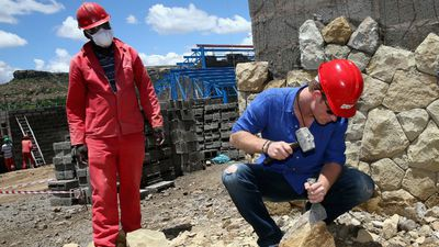 Prince Harry also got his hands dirty, helping with sandstone cladding for the guardhouse as he visits the construction site for the new Sentebale Mamohato Children's Centre at Thaba-Bosiu in Maseru.