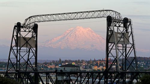Mount Rainier is seen at dusk and framed by the Murray Morgan Bridge in downtown Tacoma, Washington. (Picture: AP)