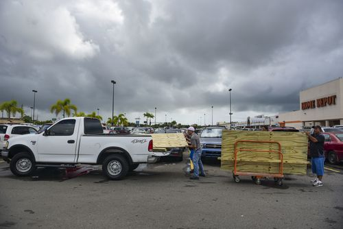Men load recently purchased wood panels to be used for boarding up windows in preparation for Hurricane Irma, in Carolina, Puerto Rico. (AP)