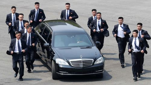File photo, North Korean security persons run by a car carrying North Korean leader Kim Jong Un return to the North side for a lunch break after a morning meeting in April with South Korean President Moon Jae-in. (AP)