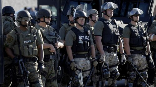 Police in riot gear watch protesters in Ferguson, Missouri, after a white police officer fatally shot Michael Brown, an unarmed black teenager, in the St. Louis suburb. (AP Photo/Jeff Roberson)