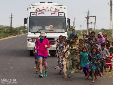 Local children running alongside Samantha during her ultra-marathon journey across India.