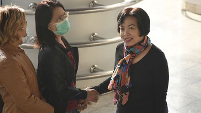 A woman identified only by her first name Anchan, right, shake hand with a friend as she arrives at the Bangkok Criminal Court in Bangkok, Thailand, Tuesday, Jan. 19, 2021