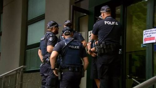 Officers gather outside the QPS building. (9NEWS)