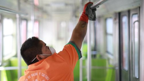 A workers disinfects a metro train car during a cleaning day at in Mexico City, Mexico.