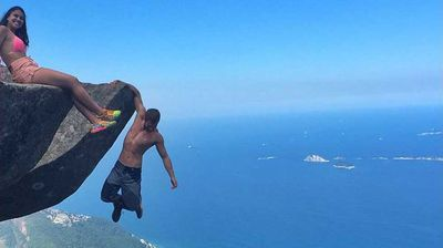 """<p>Leonardo Pereira admitted to being afraid the first time he ever allowed himself to dangle from the almost 1km-high cliff of Pedra da Gavea in Rio de Janeiro, Brazil.</p><p>  """"The first time I was a bit scared,"""" Mr Pereira told ABC News. """"I just sit down, but the next time I hang off and make Victoria do the same thing.""""</p>"""
