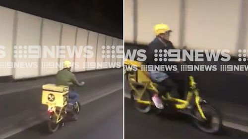 Two delivery drivers on electric bikes have been caught on camera driving through Sydney's busy Eastern Distributor tunnel. (Supplied)