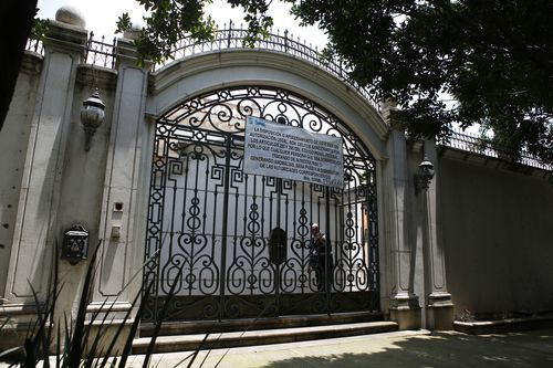 An iron gate shields the mansion from view.