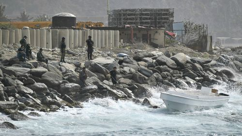 Security forces guard the shore area and a boat in which authorities claim a group of armed men landed in the port city of La Guaira, Venezuela