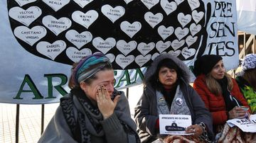 "Lucia Zunda Meoqui, sister of Adrian Zunda Meoqui, left, an Argentine Navy officer of the ""ARA San Juan"" submarine that sank and disappeared on Nov. 15, 2017, cries as she and others chain themselves to the fence of Government House in Buenos Aires, Argentina, Thursday, June 28, 2018. They are demanding that the Government find the ship. (AP Photo Jorge Saenz)"