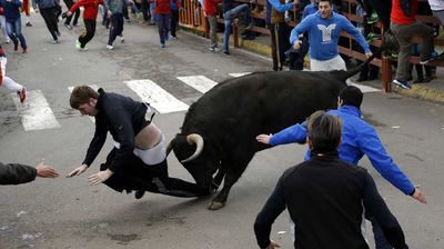 Benjamin Miller, 20, from Georgia, in the US, is gored by a bull during the 'Carnaval del Toro' in Ciudad Rodrigo, Spain. (AAP)