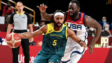 Boomers star Patty Mills is guarded by Draymond Green.