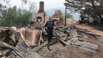 A police officer inspects one of the burnt out buildings on Colin's property.