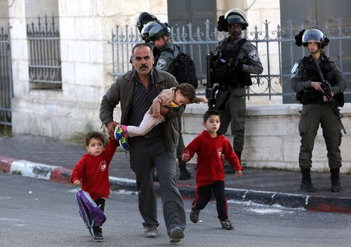 A Palestinian man and children walk past Israeli soldiers during an anti-Israel protest by Palestinians in the West Bank city of Bethlehem.
